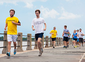 A Charleston Steeplechase Tour group runs along the boardwalk at White Point Gardens.
