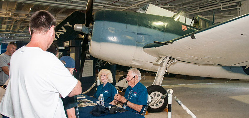 Fighter pilot Lt. Bill Watkinson flew the same aircraft Vice Admiral James Flatley Jr. did in WWII. Here he sits with Connie Reynolds answering questions in the USS Yorktown hanger. © 2016 Audra L. Gibson.