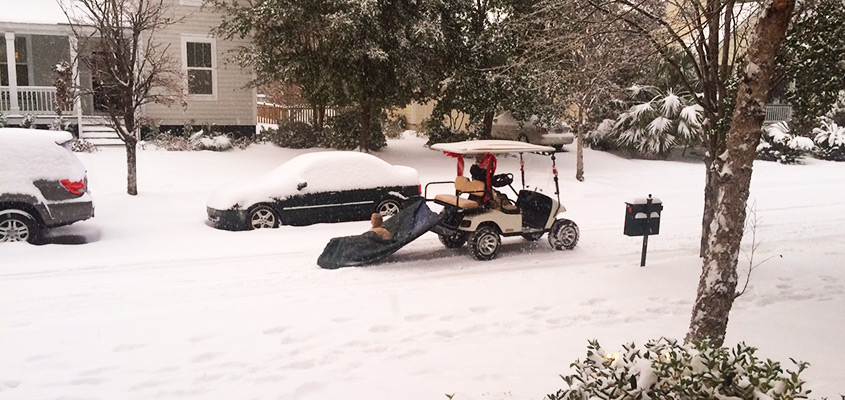 Golf cart pulls a tarp to give someone a ride in the snow in Charleston SC. © 2018 Audra L. Gibson.