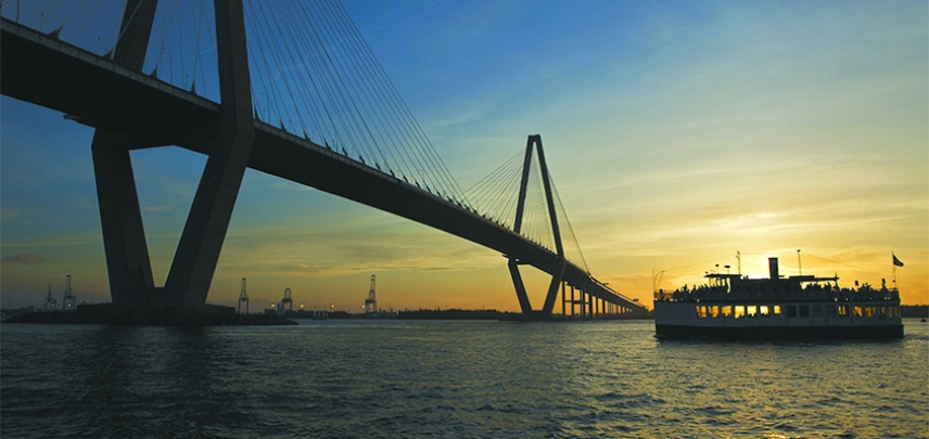 The Carolina Belle slips under the Ravenel Bridge at sunset.