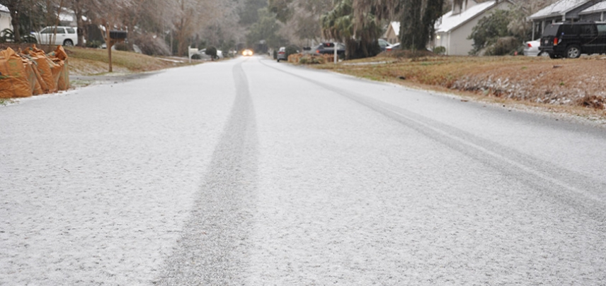 Light snow accumulates on a residential Charleston road.